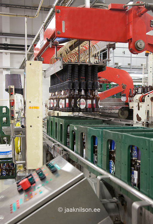 Bottling machine with moving belts with rows of bottles. Automatic process, production line. Picker lifting bottles into green crates.