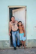 Father and Son pose in Trinidad, Cuba neighborhood.