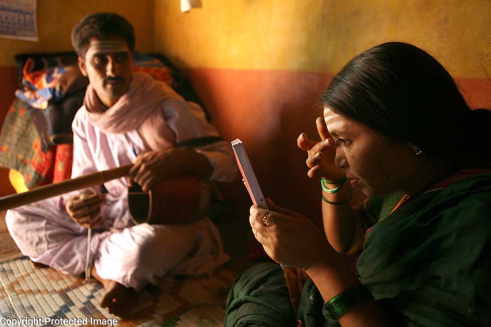 "Radhabai Madar Mudalagi (right) was dedicated as a Devadasi by her parents at a very young age.  Now in her early forties, she lives in the small village of Yellamanawadi and uses the Devadasi musical tradition called ""Chowdike Pada"" to educate her audiences about social issues, particularly, the Devadasi system. Accompanied by her husband, Mrutunjaya Mudalagi, (left) who plays an instrument called the shruti that resembles a guitar, Radhabai was even recorded for a television program which was broadcasted to small villages all over Karnataka and other states as part of a social education program.  Because of her activism coupled with the fact that she defied the Devadasi system and married a man, she has been rejected by her community. ."