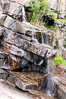 Ticino, Southern Switzerland. Waterfall at Ponte Brolla.  Water cascades down the rocky outcrops with small plants clinging to the rock crevices.