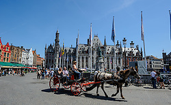 Horse drawn carriage carrying tourists in Grote Markt, Bruges, Belgium<br /> <br /> (c) Andrew Wilson | Edinburgh Elite media