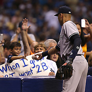 New York Yankees shortstop Derek Jeter (2) hands a ball to a young fan between innings during a major league baseball game between the New York Yankees and the Tampa Bay Rays at Tropicana Field on Thursday, Sept. 17, 2014 in St. Petersburg, Florida. The Yankees won the game 3-2 and this was Jeter's last game against Tampa Bay. (AP Photo/Alex Menendez)