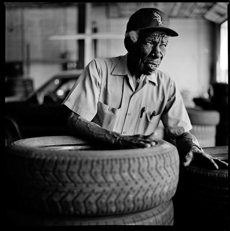 "L.C. Caviness, 78, presides over used tire sales at National Brake & Alignment on a stretch of Truman Road where he has worked for 60 years. ""You gotta understand the people....I have a story for everybody....I can make 'em laugh, I can make 'em cry."""