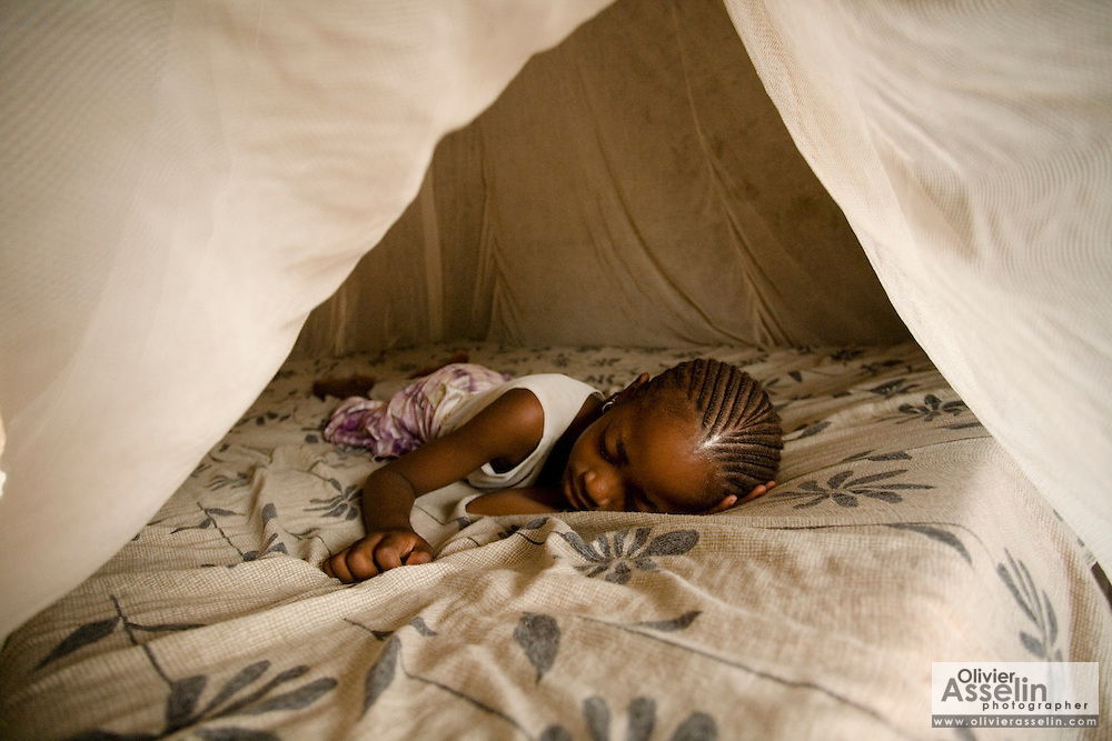 A girl sleeps under a mosquito net in the village of Bonconto on Tuesday June19, 2007.