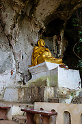 Interior view of a large Buddha statue within the famous Pak Ou Caves, Laos, along the Mekong River.