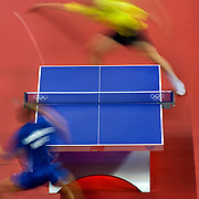 Yo Kan of Japan, top, returned a shot against Russia's Alexei Smirnov, bottom, in the men's singles table tennis competition at the Peking University Gymnasium during the 2008 Summer Olympic Games in Beijing, China. (photo by David Eulitt/The Kansas City Star/MCT).