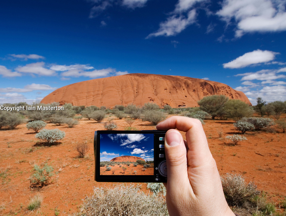 Tourist photographing Uluru in Australia with a digital  camera