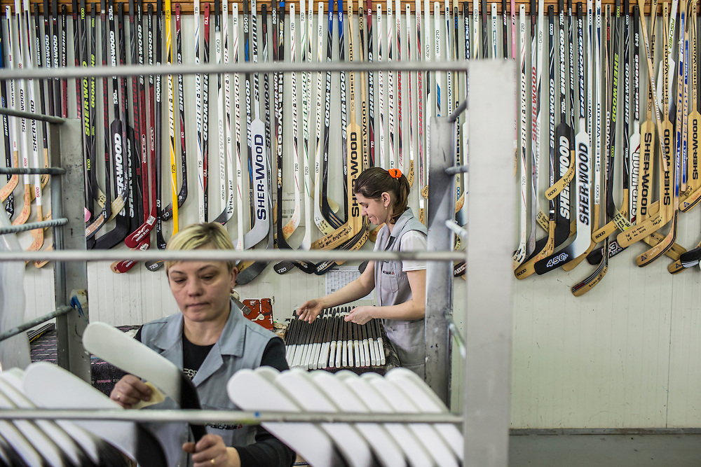 MUKACHEVO, UKRAINE - FEBRUARY 25, 2016: Workers at the Fischer-Mukachevo factory attend to final steps in manufacturing hockey sticks in Mukachevo, Ukraine. The plant fabricates skis as well as hockey sticks, many of which are produced for export. CREDIT: Brendan Hoffman for The New York Times