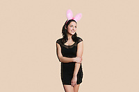 Happy young woman wearing rabbit ears looking away over colored background