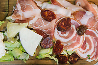 "NAPLES, ITALY - 10 OCTOBER 2018: A starter dish made of raw shoulder, cold cuts of Castelpoto and cheese produced by Giovanni Pucciarelli, are seen here at La Taverna a Santa Chiara, a tavern in the historical center of Naples, Italy, on October 10th 2018.<br /> <br /> The idea of the founders Nives Monda and Potito Izzo (two really unusual names in southern Italy) was to create a ""taste gate"" of Campania products. La Taverna a Santa Chiara, founded in 2013, is a modern tavern whose strengths are the choice of regional and seasonal products and mostly small producers. Small restaurant, small producers.<br /> The two partners tried to put producers and consumers in direct contact, skipping the distribution, and managing to reduce the costs of the products considerably. Nives and Potito managed to create a simple kitchen, at moderate costs but with high quality raw materials.<br /> ""A different restaurant idea,"" says Nives, ""the producers deliver their products at low prices and the tavern manages to make traditional dishes with niche products"".<br /> Nives Monda has been a labor consultant for 20 years. Potito Izzo is the chef who has always been loyal to the  family cuisine. When he embraced the idea of Nives he found in the tavern the natural place to express the tradition of Neapolitan cuisine. Nives defines him as a ""comfort food chef"". Their partnership is a true friendship that has lasted for over 10 years."