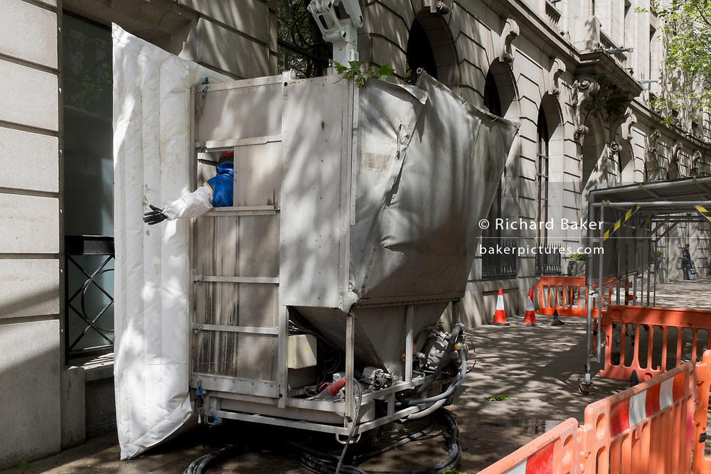 A machine operator gives a hand signal to a crane driver from inside enclosed equipment cleaning the stone work surfaces of an address in Aldwych WC2, on 2nd May 2019, in London, England.