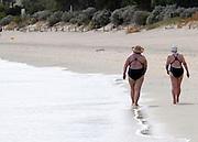 AUSTRALIA - BANBURY Two women swimmers stroll along the beech at Banbury, Western Australia. 10/01/2010. STEPHEN SIMPSON...