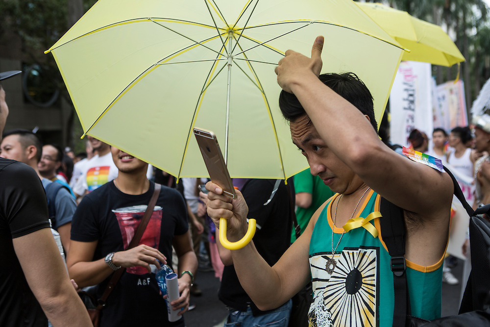"A man checks his hair before taking a ""selfie"" at LGBT Pride."