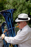 Man in a brass band wearing a white straw panama hat playing a blue laquered tuba ....