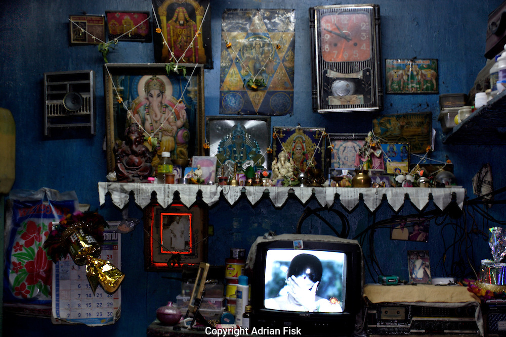 A Bollywood film plays on a TV in the one room home of this south Indian family.