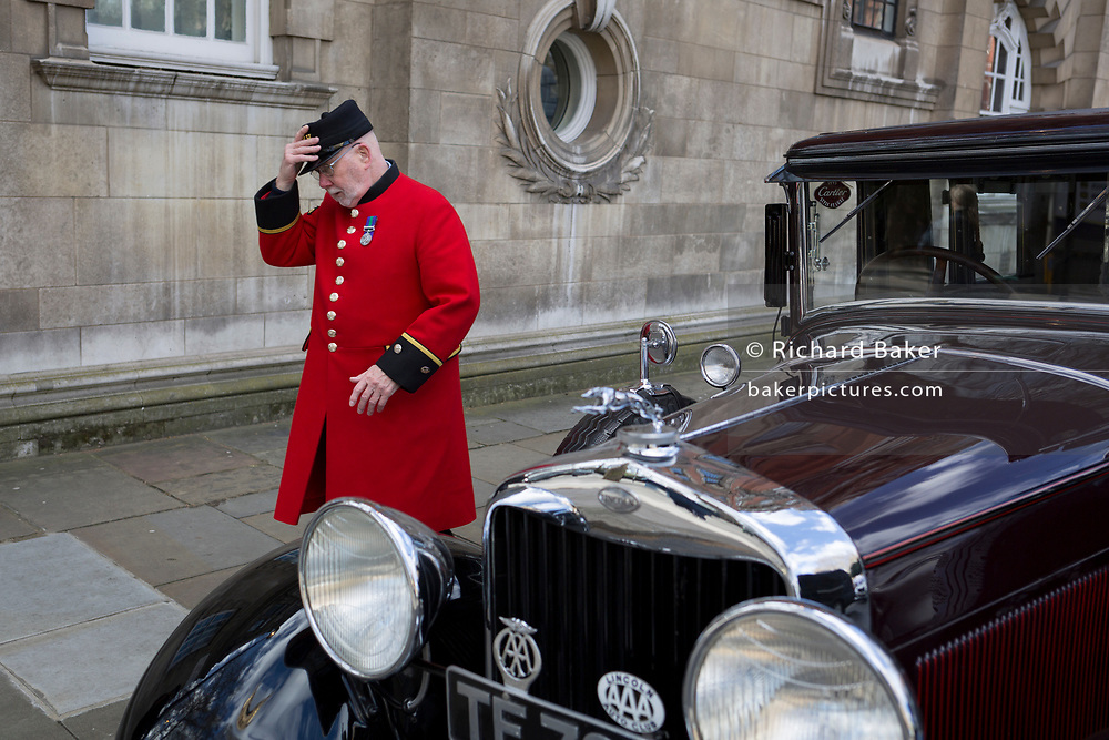A Chelsea Pensioner replaces his uniform cap in front of a classic Lincoln car in Westminster, on 11th March 2019, in London, England.