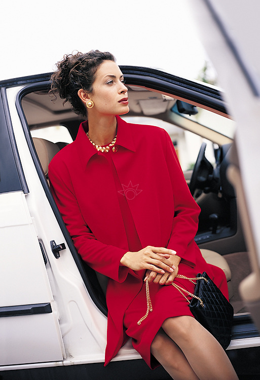 Photograph of a women dressed in red, waiting in a white car. Image created for Charles Keath.