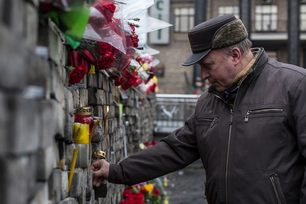 KIEV, UKRAINE - FEBRUARY 23: A an places a candle at a memorial to anti-government protesters killed in chashes with police on Independence Square on February 23, 2014 in Kiev, Ukraine. After a chaotic and violent week, Viktor Yanukovych has been ousted as President as the Ukrainian parliament moves forward with scheduling new elections and establishing a caretaker government. (Photo by Brendan Hoffman/Getty Images) *** Local Caption ***
