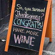 "Blackboard humorous  wine store sign, ""So, you survived Thanksgiving? CONGRATS. Have More WINE."""