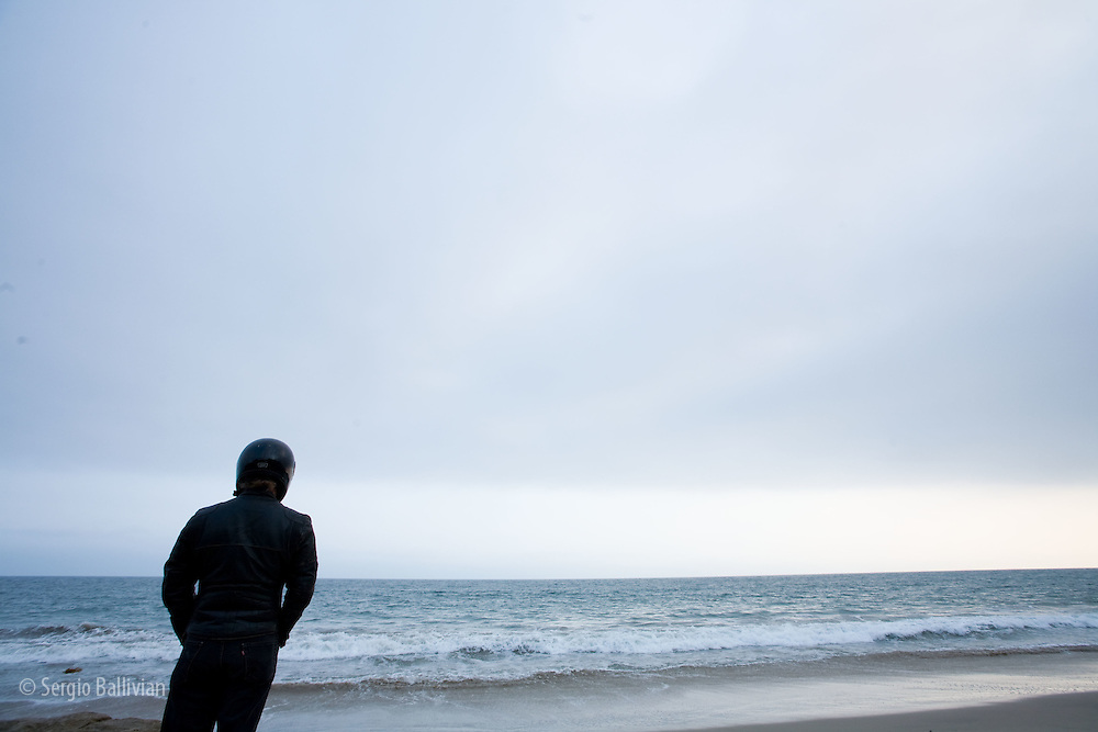 A solitary individual contemplating the ocean on a beach in Malibu, CA