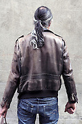 male person with ponytail standing in front of a blind wall
