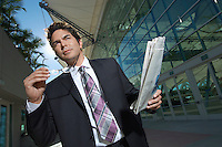 Businessman with newspaper outside office building