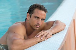 handsome man with blue eyes leaning against the side of a swimming pool