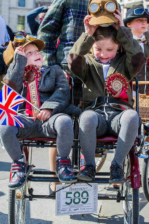 """Jonty, 3 and his sister Poppy, 7, await the start. The Tweed Run 2015 - it's 7th annual British public bicycle ride through London's historic streets, with a prerequisite that participants are dressed in their best tweed cycling attire. There are also plenty of handle bar moustaches, penny farthings and Union Jacks. """"Guests can expect a leisurely day cycling, stopping at some of London's most iconic landmarks to enjoy a spot of tea, a picnic in the park and finally a jolly good knees-up in a beautiful art-deco ballroom for the Tweed Run closing ceremony. Starting at Trafalgar Square, the cyclists then embarked on a 12 mile scenic ride through London, stopping at traditional spots."""