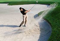 A young man making a sand shot on a golf course.