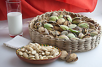 a composition with almonds in a basket, shelle and in a shell with a glass of almonds milks. All the almonds in several steps of working in a fine art pictgure