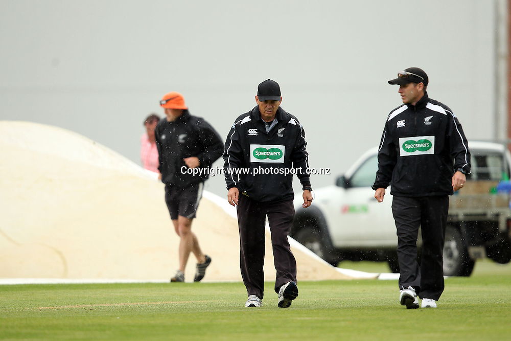 Chris Gaffaney and Barry Frost leave the field due to a rain interruption at the University Oval.<br /> Twenty20 Cricket - HRV Cup, Otago Volts v Northern Knights, 29 December 2011, University Oval, Dunedin, New Zealand.<br /> Photo: Rob Jefferies/PHOTOSPORT