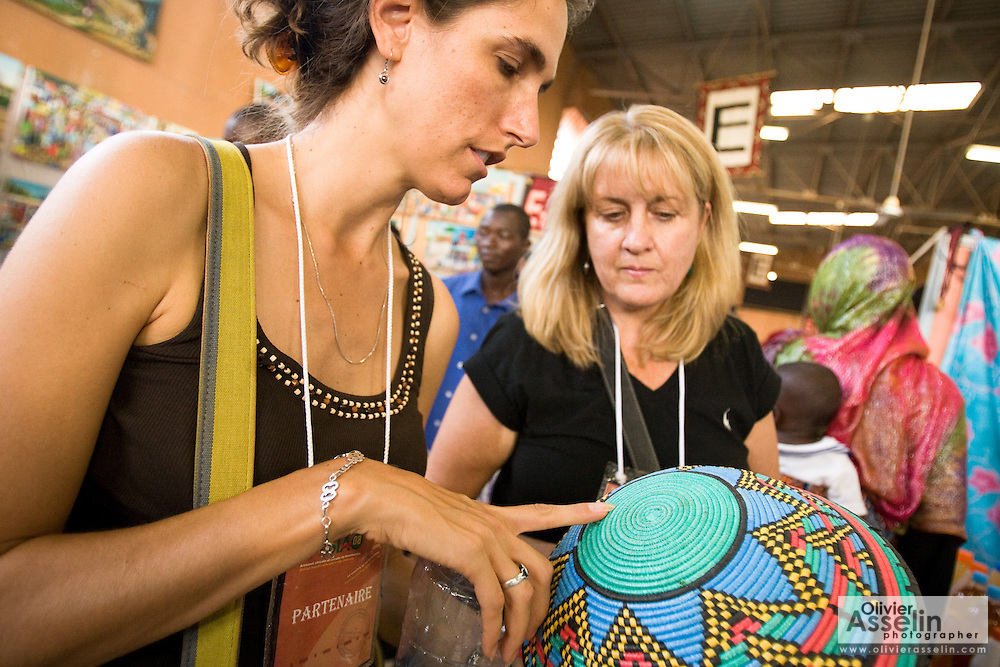 Professional buyers looks at a basket at the 22nd Salon International de l'Artisanat de Ouagadougou (SIAO) in Ouagadougou, Burkina Faso on Sunday November 2, 2008.