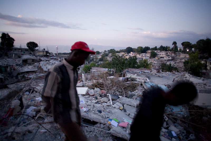 Men collect small items and look through the rubble of their collapsed homes before walking back to their IDP camp to sleep. Nerrettes, Port Au Prince, Haiti. 1/19/2010 Photo by Ben Depp.