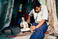 A man hammers together a small buddha statue in the back alleys of Patan, Nepal.