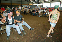 A woman about to wrestle in chocolate sauce flashes the patrons at a Harley-Davison anniversary party in Milwaukee August 29, 2003. The legendary American motorcycle company is celebrating its 100th anniversary and is expected to draw 200,000 to 300,000 people to the companies home base over four days.    REUTERS/Rick Wilking