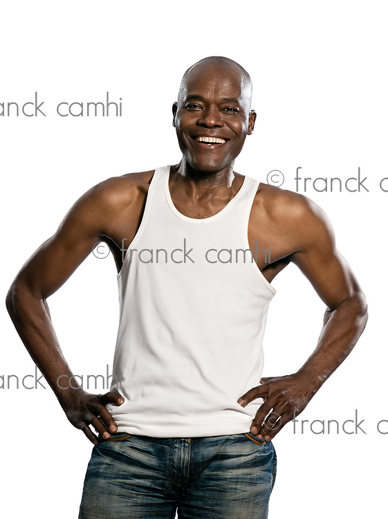 Portrait of a laughing afro American mature man with hands on waist standing in studio on white isolated background