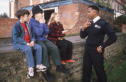 Community police officer standing in street talking to group of young children,