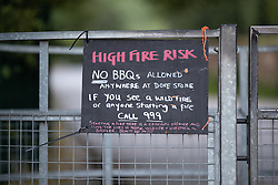 "© Licensed to London News Pictures . 28/06/2018 . Saddleworth , UK . Warnings of a high fire risk posted on gates around Dove Stone reservoir as the army are being called in to support fire-fighters , who continue to work to contain large wildfires spreading across Saddleworth Moor and affecting people across Manchester and surrounding towns . Very high temperatures , winds and dry peat are hampering efforts to contain the fire , described as "" unprecedented "" by police and reported to be the largest in living memory . Photo credit: Joel Goodman/LNP"