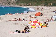 Sunbathers and swimmers at Lozari Beach.