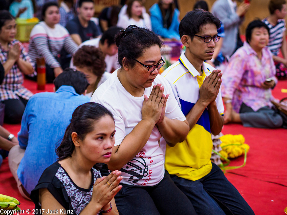 31 MAY 2017 - CHACHOENGSAO, THAILAND: People pray at Wat Sothon (also spelled Sothorn) in Chachoengsao, Thailand. The temple is one of the largest and most visited in Thailand. People make merit by paying to wrap the Buddha statues in orange robes. The temple is most famous because people leave hard boiled eggs as an offering at the temple. They ask for business success or children and leave hundreds of hard boiled eggs.      PHOTO BY JACK KURTZ