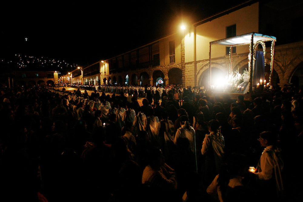 A procession for Saint Mary around the Plaza de Armas (www.britannica.com/eb/topic-35092/Plaza-de-Armas) in Ayacucho, Peru, (lat -13.1548°, long -74.2044°, Altitude: 9,202 Feet - http://www.fallingrain.com/world/PE/5/Ayacucho.html), Wednesday night, May 14, 2008. There are many processions for various saints in the city of Ayacucho, peaking with the holy week of Semana Santa in May (overly dramatic promotional video - http://www.youtube.com/watch?v=6pwdhC_xu-w). This procession began at the Cathedral and wound around the Plaza de Armas with stops at each corner for the ceremonial ?lighting of the bottle rocket,? and one big tower of fireworks and sparks that rained down on the crowd. Saint Mary herself was lit with a high-wattage electric light powered by a gas generator being carted behind her; it?s electrical cord snaked through the crowd. The path for St. May was lined with candle-holding children from the main catholic school in Ayacucho. Some of the children had to move out of formation when the ?glowing halo of fire? that launched from the ceremonious tower of fireworks came streaming back down to earth, narrowly missing them and the 17th century building that encompass the plaza.
