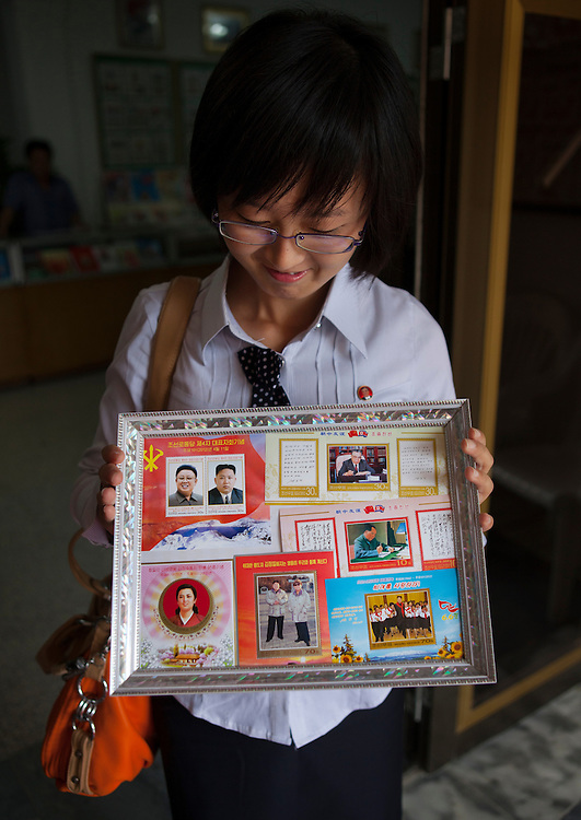 -I want to offer you a gift, what would you like?<br /> -Great leader Kim Jung Un would be a great gift...<br /> <br /> North Korean woman showing Kim Jun Un stamps in Kaesong, North Korea.<br /> <br /> Miss Kim is 20. She lives in Pyongyang, North Korea's display window. She's studying English. First of her class, she was lucky enough to come with me during my 6th trip to North Korea as an assistant guide. She had never previously left Pyongyang. It was a unique opportunity for her to visit her own country and to get to meet and speak to a foreigner. She was shy at first, but became quite talkative as the days went on, and describe to me the everyday lives of young North Koreans. Without ever crossing over the Party line...<br /> <br /> Small chats between friends who will never meet again...<br /> <br /> Eric Lafforgue