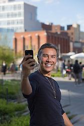Asian American man enjoying himself by taking a selfie in New York City