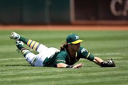 OAKLAND, CA - JULY 23:  Josh Reddick #22 of the Oakland Athletics dives for and catches a foul ball hit off the bat of Devon Travis (not pictured) of the Toronto Blue Jays during the sixth inning at O.co Coliseum on July 23, 2015 in Oakland, California. The Toronto Blue Jays defeated the Oakland Athletics 5-2. (Photo by Jason O. Watson/Getty Images) *** Local Caption *** Josh Reddick