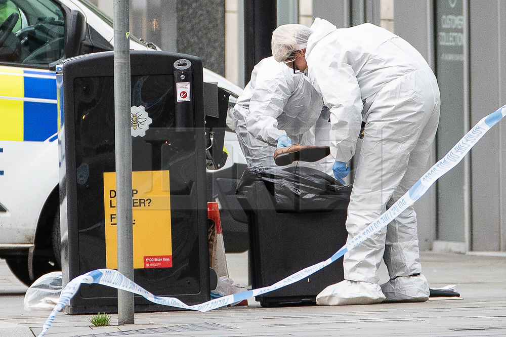 © Licensed to London News Pictures. 11/10/2019. Manchester, UK. Forensic scenes of crime examiners remove a shoe from a bin at the foot of the steps to the Arndale Centre in Exchange Square . Terrorism Police are investigating after four people were stabbed during a single attack at the Arndale Centre in Manchester City Centre . Photo credit: Joel Goodman/LNP