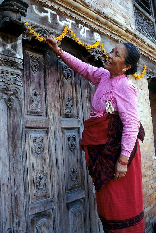 Asia, Nepal, Kathmandu Valley, Bhaktapur. Woman hangs garland of marigolds to honor Hindu Goddess during Tihar Dipawali festival.