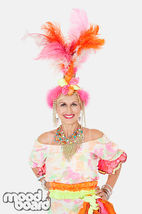Portrait of happy senior woman in Brazilian outfit over gray background