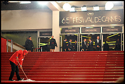 Festival staff brush water off the Red Carpet after heavy rain during the 65th Annual Cannes Film Festival at Palais des Festivals, Cannes, France, Sunday May 20, 2012. Photo by Andrew Parsons/i-Images.