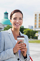 Portrait of young attractive businesswoman smiling while holding a cup of coffee outside office building