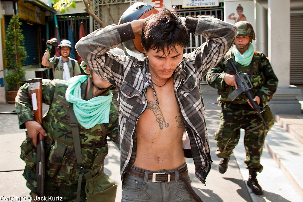 14 MAY 2010 - BANGKOK, THAILAND: Thai soldiers arrest a man who had used a slingshot to launch rocks and small explosive ping pong balls towards troops on Rama IV Road in Bangkok Friday. Thai troops and anti government protesters clashed on Rama IV Road Friday afternoon in a series of running battles. Troops fired into the air and at protesters after protesters attacked the troops with rocket and small homemade explosives. Unlike similar confrontations in Bangkok, these protesters were not Red Shirts. Most of the protesters were residents of nearby Khlong Toei slum area, Bangkok's largest slum area. The running battle went on for at least two hours.   PHOTO BY JACK KURTZ